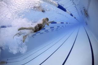 ジムのプールで水泳する人